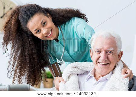 Caregiver Covering Elderly Man With Blanket