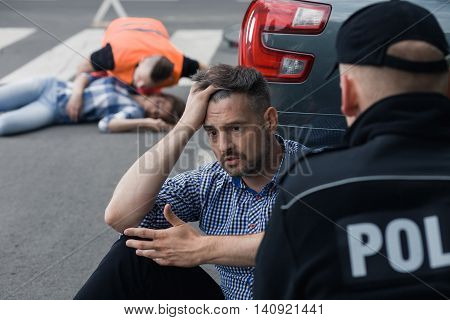 Anxious man sitting in front of the police officer with the victim of a crash at the background