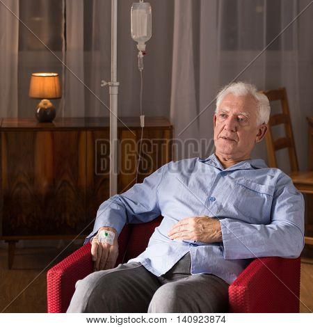 Elder patient with terminal illness sitting in an armchair