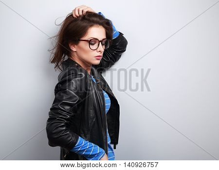 Sexy Woman Posing In Fashion Black Leather Jacket And Eye Glasses On Blue Background