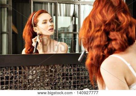 Red-haired Girl Looking In The Mirror And Applying Cosmetic With A Big Brush.