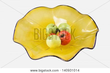 Dusty yellow glass bowl on white background with apples and tomatoes.