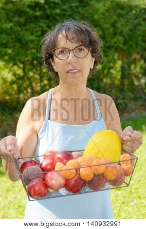 a mature woman with a blue dress and a fruit basket