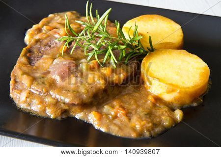 black dish with braised meat with polenta