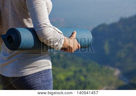 Woman standing with yoga mat outdoors in mountains close up with copyspace