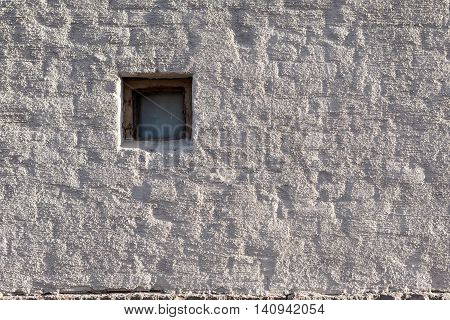 Plastered brick wall and small window outside