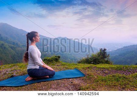 Yoga exercise outdoors -  woman doing Yoga asana Virasana Hero pose in Himalayas in India on sunset