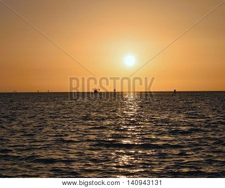 A boat coming in during a golden sunset at Hudson beach in Hudson, Florida.