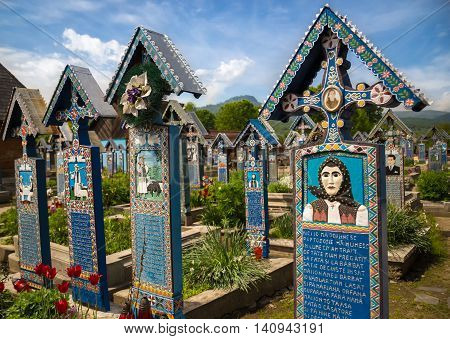 SAPANTA ROMANIA - MAY 16 2015 - Colorful painted wooden tombstones at Merry Cemetery Famous graveyard in county of Maramures Romania
