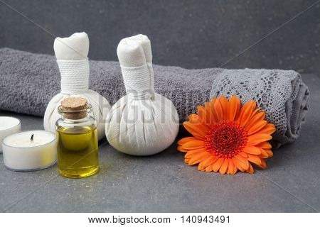 SPA still life with towels, oil, massage balls and gerbera flowers on a grey background
