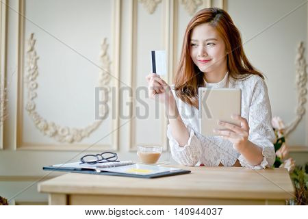 Happy Woman Shopping Online, Holding Credit Card, Using Tablet Computer.
