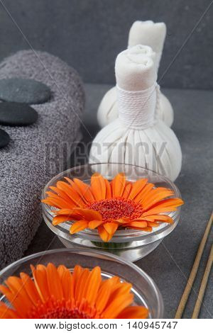 Spa massage setting with rolled towel, thai herbal compress balls and flowers on grey surface