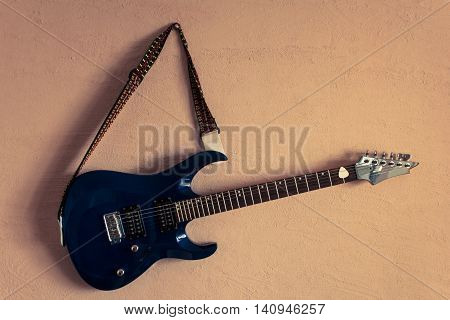 electric guitar on a background of vintage beige wall.