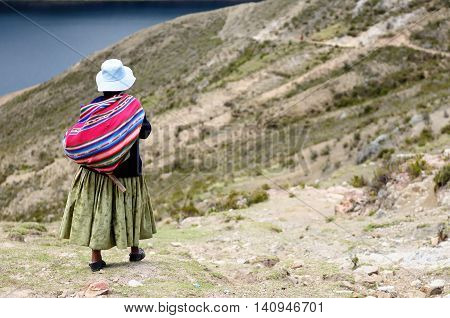 South America Bolivia - Isla del Sol on the Titicaca lake the largest highaltitude lake in the world. Woman standing in the traditional dress on the lake Titicaca