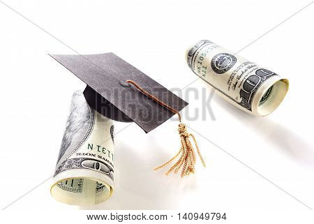 miniature graduation cap and hundred dollar bills