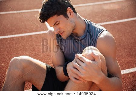 Close up portrait of a runner suffering from leg cramp on the track at the stadium