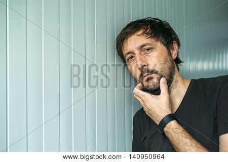 Pensive adult unshaven man with hand on chin thinking hard judging or evaluating something studio portrait with copy space