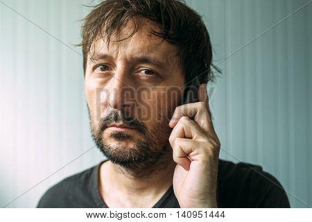 Tired adult man talking on mobile phone studio indoors portrait