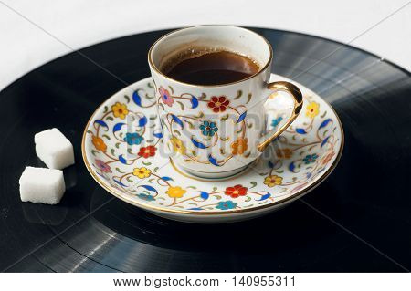 Cup of black coffee on surface of music vinil plate. Sound of morning concept.