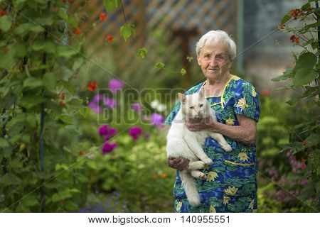 Elderly woman in garden with cat on hands.