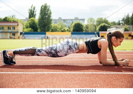 Slim beautiful athletic woman doing planking exercise in the stadium