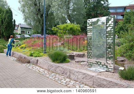 KOTKA, FINLAND - JUNE 26, 2016: Woman take pictures in Sapokka Water Garden. It is most ecological center in the town. Foreground is sculpture composition by Eero Hiironen