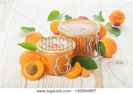 Apricot jam and fresh fruits on the rough wooden background