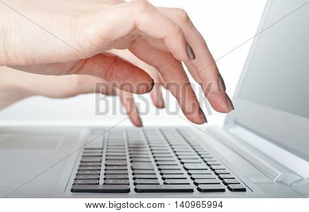 Female hands are typing on the keyboard.