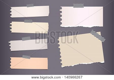 Pieces of ripped colorful notebook paper are stuck with sticky tape on dark gray background.