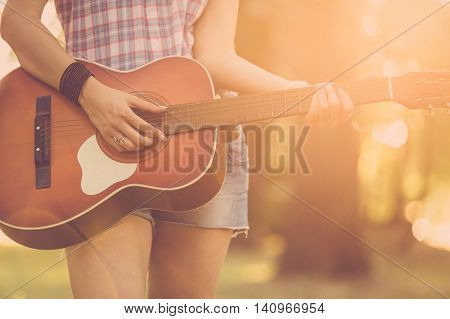 Close up of female hands playing acoustic guitar in nature. Retro, music, lifestyle concepts.