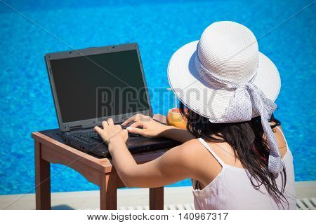 Young woman using laptop with blank screen at the poolside. Freelance and working on vacation concepts.