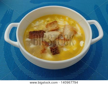 Delicious soup with croutons and sour cream in a white bowl,which stands on a blue tablecloth