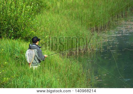 Closeup Of Fisherman Fly Fishing