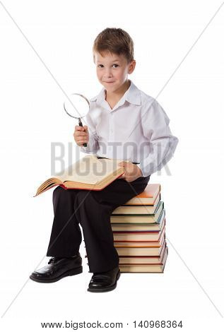 Smiling boy sitting on pile of books reading old book with magnifier in hand, isolated on white