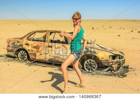 hitchhiker woman for fun in the desert with a car wreck burned on background