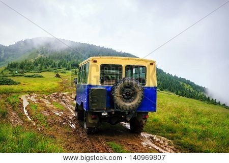 Off-road car rides on the swamp road in the mountains at rain weather Carpathians Ukraine