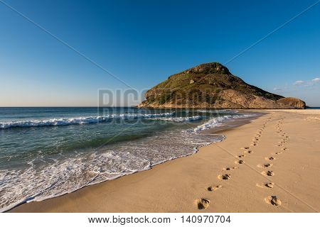 Footsteps in Sand in Recreio Beach and Pontal Rock in the Ocean, Rio de Janeiro, Brazil