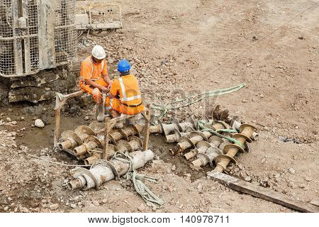 ILKESTON ENGLAND - AUGUST 1: Construction workers sitting next to a pile drilling machine on a railway side site. In Ilkeston Derbyshire England. On 1st August 2016.
