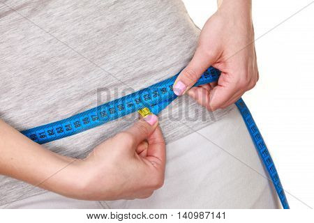 Weight loss. Woman fit girl measuring her hips with blue measure tape closeup. Part of female body isolated on white.