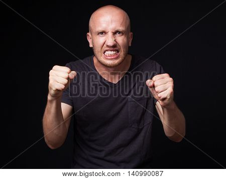 Close up portrait of an angry bald man shaking his fists black background