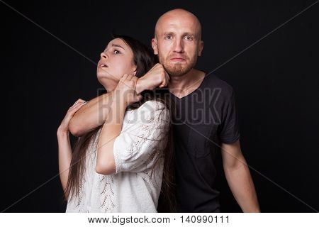 Domestic violence - man detaining woman black background