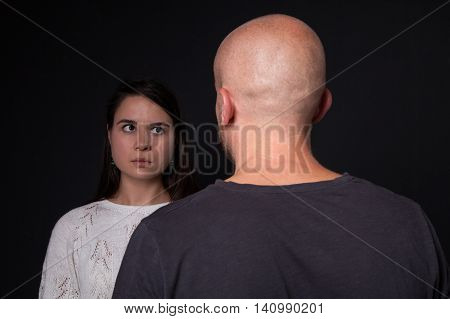 Young scared woman looking at man he is standing back to the camera black background