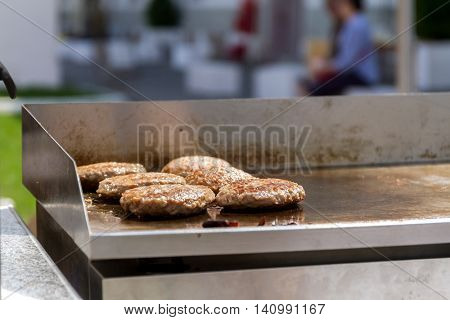 hamburgers and hotdogs cooking on grill outdoors