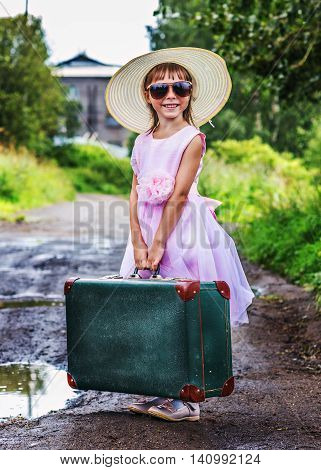 Little girl standing with a suitcase on a rural road and waiting for transport.