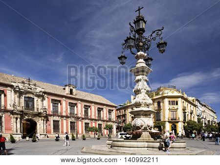 SEVILLE, SPAIN - September 13, 2015: Tourists passing by the marvellous water fountain and lamp at the Plaza Virgen de los Reyes on September 13, 2015 in Seville, Spain