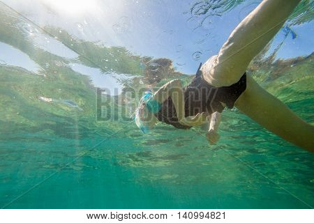 Young female snorkeling in tropical blue sea.