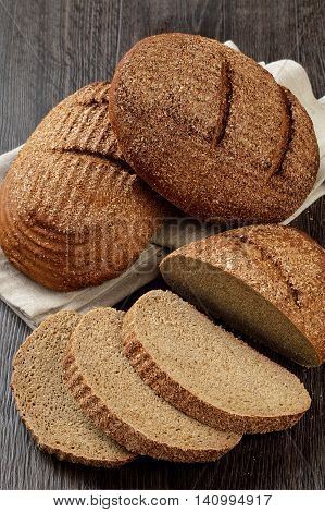 Two loaves of rye bran bread with slices on wooden background