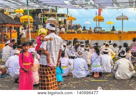 Bali,Indonesia-May,28, 2010:Balinese man bringing his daughters attending the prayer at Tanah Lot temple, Bali on 28th May 2010.The temple has been part of Balinese mythology for centuries.