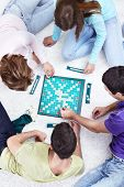 foto of scrabble  - Young people play Scrabble on the floor - JPG