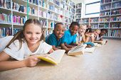 Smiling school kids lying on floor reading book in library at elementary school poster